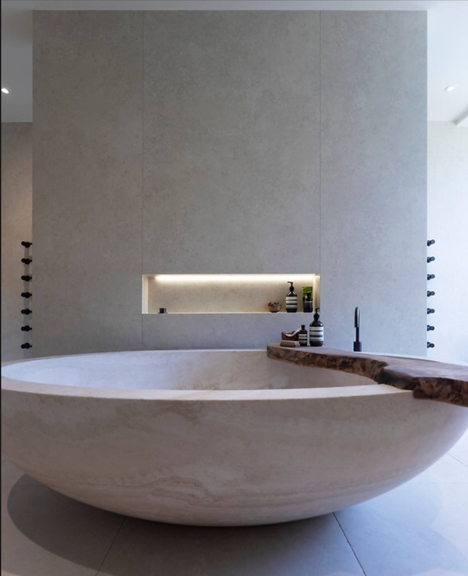 A picture of a stone bath in the centre of a master bathroom suite