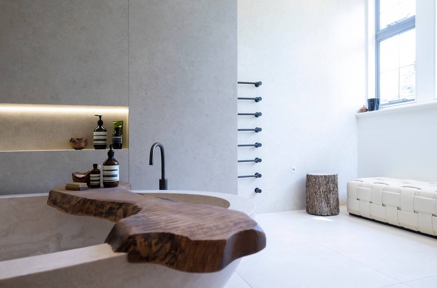 A picture of a stone bath in a bathroom with a popla wood top